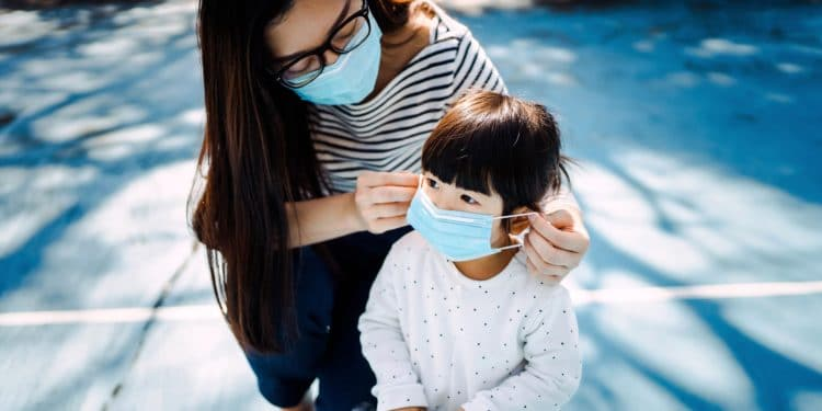 Young mother putting on surgical mask for little daughter in the playground to prevent the spread of cold and flu and viruses
